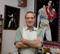 Man standing near pictures of elvis in his accommodation