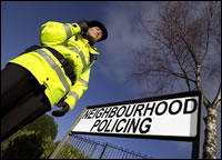 Police lady stood by Neighbourhood Policing sign