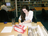 Photograph of one of our volunteers handling archive material